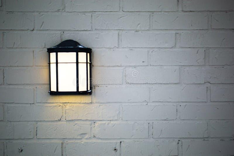 Appareil d'éclairage rustique sur le fond blanc de mur de briques image stock