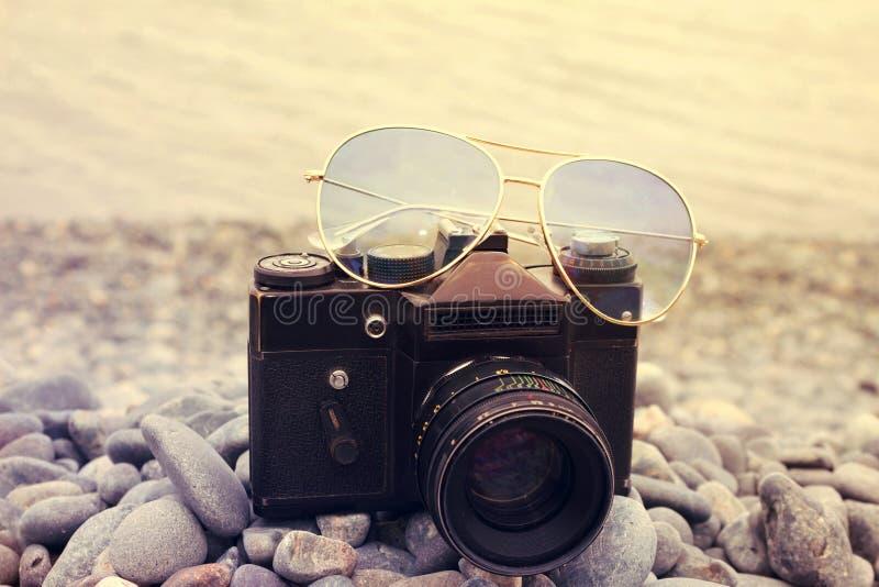 Appareil-photo avec la pousse haute étroite en verre de soleil sur une plage de mer Rétro VCA image stock