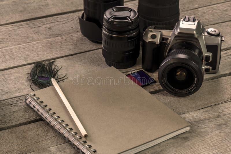 Appareil-photo de photo avec la lentille à côté du carnet photo stock