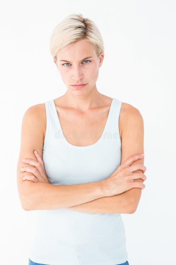 Appareil-photo de regard blond bouleversé avec des bras croisés photographie stock