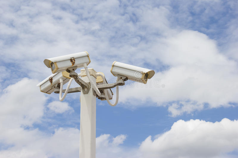 Appareil-photo de télévision en circuit fermé à l'arrière-plan nuageux de ciel bleu images stock