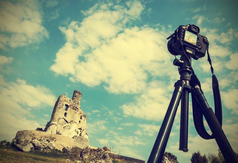 Appareil-photo sur le trépied avec le paysage d'été avec des ruines, vintage images stock