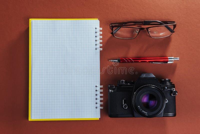 appareil-photo, verres et bloc-notes et crayon sur un fond en bois brun photographie stock libre de droits