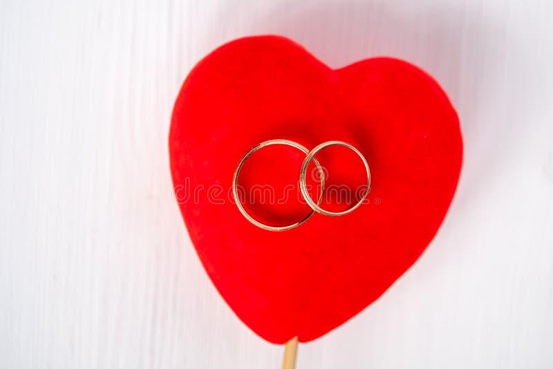 Appareillez épouser des anneaux d'or sur le coeur rouge de velours sur le fond blanc Projectile suppl?mentaire photographie stock