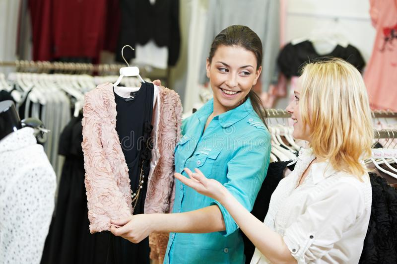 Apparel, clothing shopping. Young woman choosing dress or wear in store royalty free stock photography