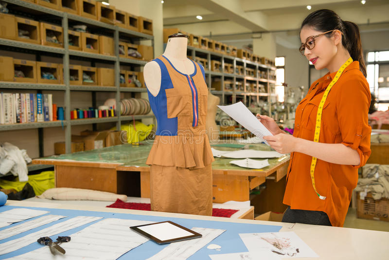 Apparel company employee holding draft design. Apparel company employee holding pattern draft design paper standing before dummy model to checking costume design royalty free stock image