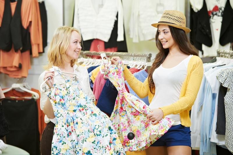 Apparel shopping. Young woman choosing dress or clothing in store stock images