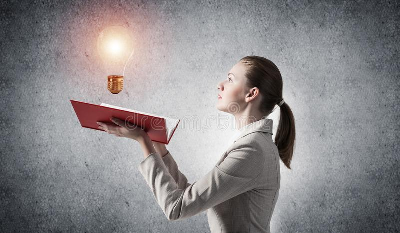 Apparence de femme brillant l'ampoule sur le livre ouvert image libre de droits