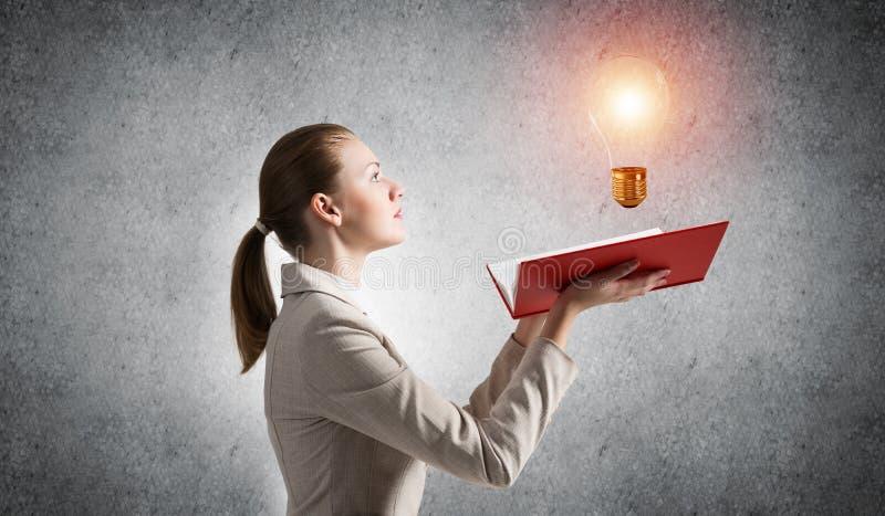 Apparence de femme brillant l'ampoule sur le livre ouvert photo stock