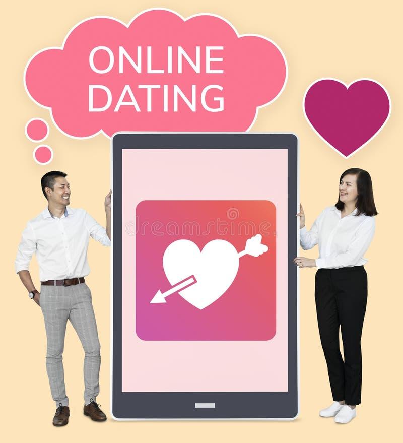 Apparence gaie de couples datant en ligne sur un comprimé photographie stock