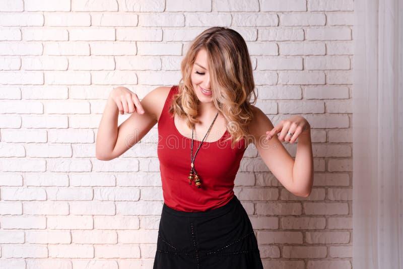 Apparence heureuse de jeune femme en bas du pointage de copyspace Jeune femelle blonde dirigeant des doigts loin L'espace de copi photo stock
