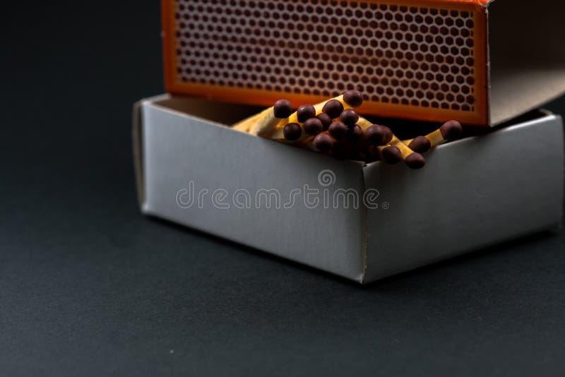 Apparence semi-ouverte de boîte d'allumettes quelques matchs Matchs et boîte en carton Fond noir image libre de droits
