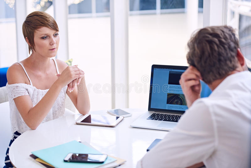 Apparent disagreement between male and female partners during business meeting stock photography
