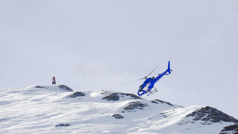 Apparent helicopter crash in a mountain ridge. A man standing o a mountain`s top looking at a helicopter flying by. The station point of the photographer gives royalty free stock images