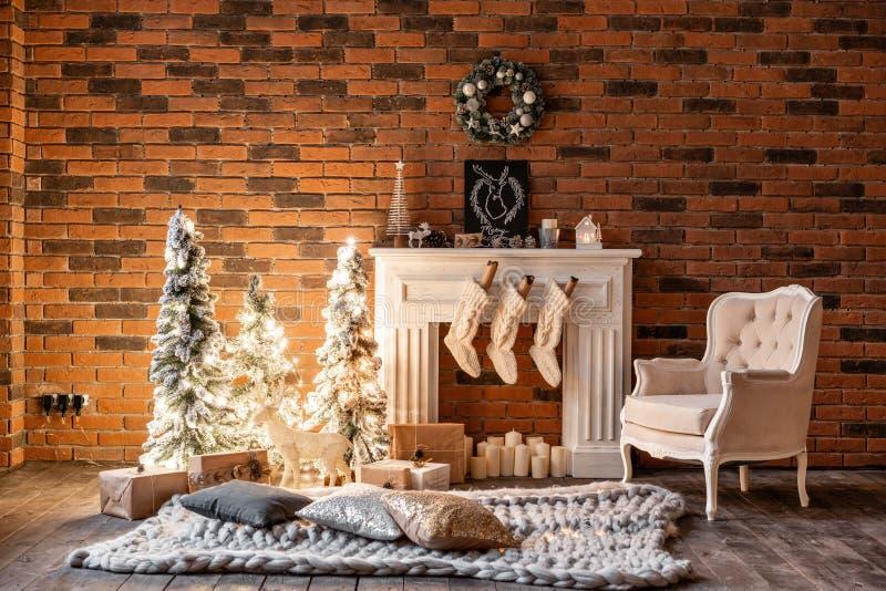 Appartamenti del sottotetto, muro di mattoni con la corona dell'albero di Natale e delle candele Calzini bianchi della lana per S immagine stock