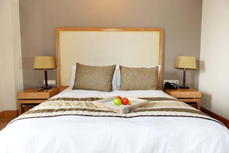 Appartamento nell'albergo di lusso con le mele sul letto fotografia stock
