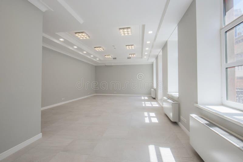 Appartamento non ammobiliato in grigio con le grandi finestre fotografia stock