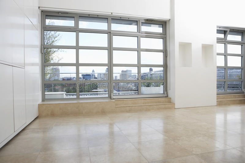 Appartamento vuoto con la pavimentazione piastrellata e Windows fotografia stock libera da diritti