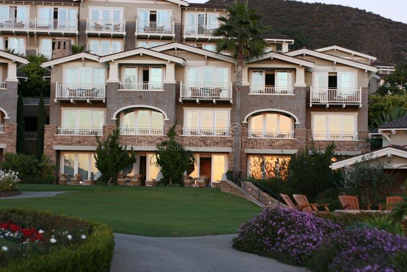 Appartements de luxe de côte pendant le coucher du soleil image stock