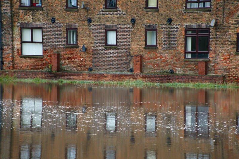 Appartements riverains reflétés dans l'eau à marée haute photos libres de droits