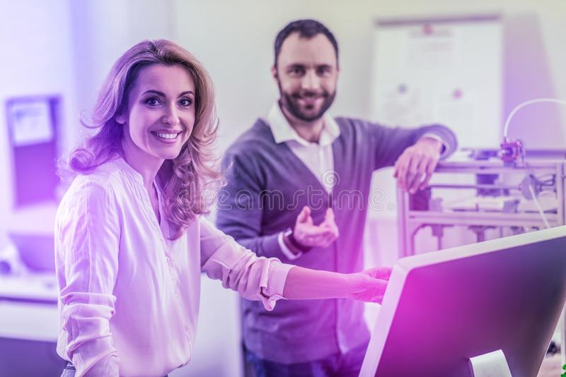 Appealing dark-eyed woman wearing beige blouse standing near her colleague royalty free stock photos
