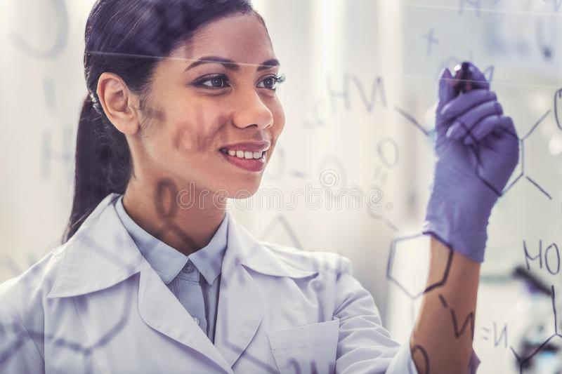 Appealing dark-haired chemist writing chemical formula. Dark-haired chemist. Appealing dark-haired chemist feeling proud of herself while writing chemical stock image
