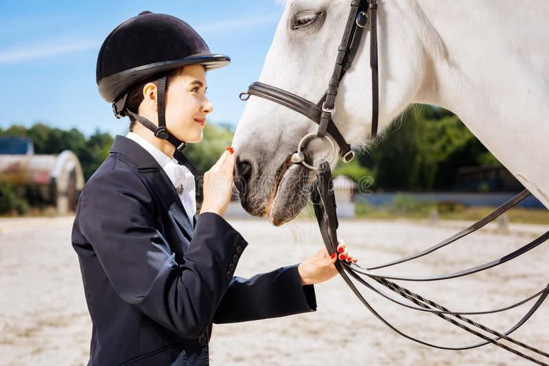 Appealing horsewoman looking into eyes of her white horse royalty free stock photo