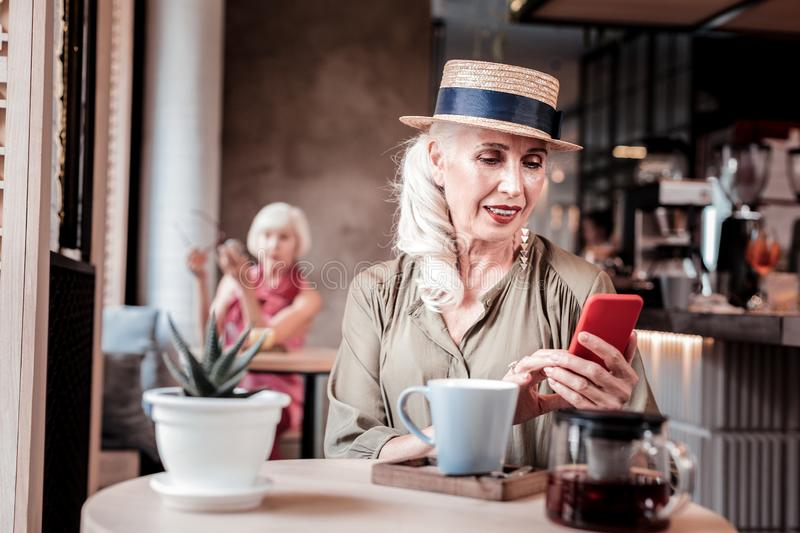 Appealing long-haired old woman in straw hat observing her smartphone royalty free stock images