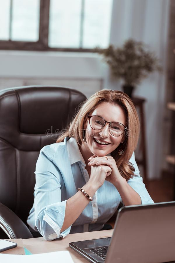 Appealing mature woman wearing nice earrings smiling at work stock photography