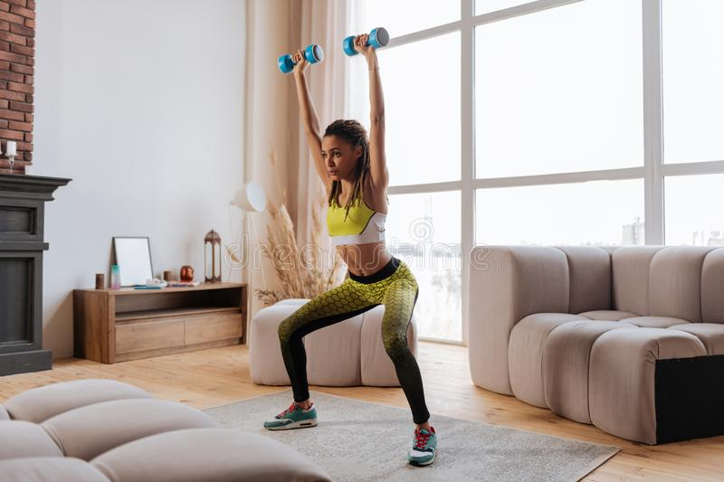 Appealing sportswoman raising her hands with blue barbells stock photography