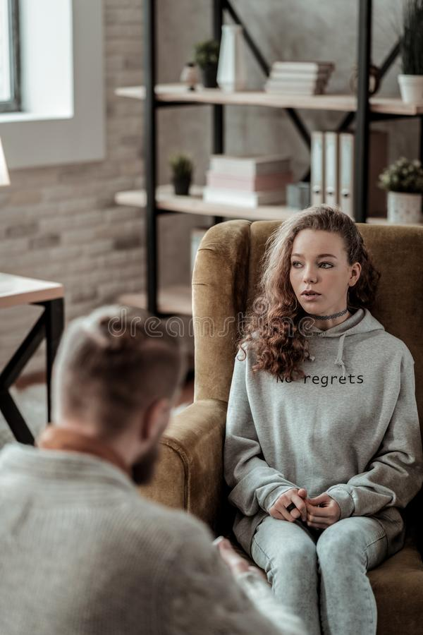 Appealing teenage girl sitting in armchair talking to counselor. Talking to counselor. Appealing stylish teenage girl sitting in armchair while talking to royalty free stock photography