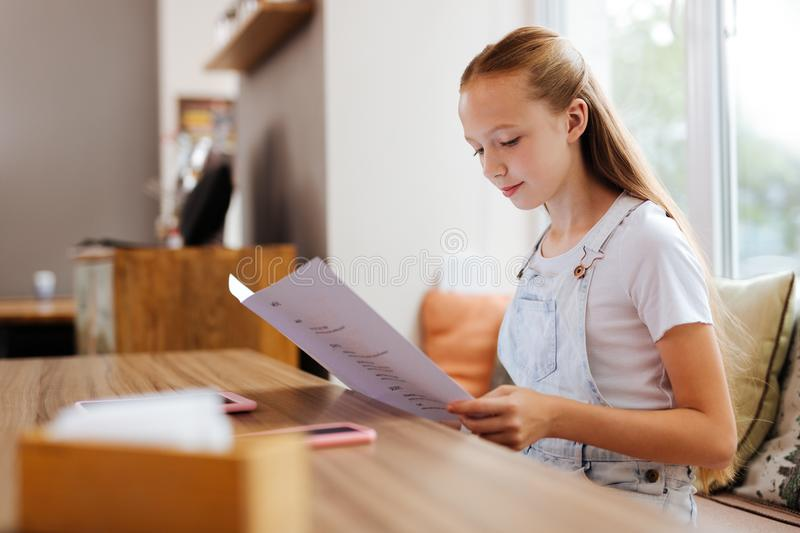 Appealing teenager with long blonde hair having some hesitations stock photography