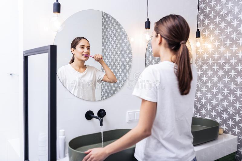 Appealing woman brushing teeth standing in the bathroom. In the bathroom. Slim appealing dark-haired woman brushing teeth standing in the bathroom royalty free stock images