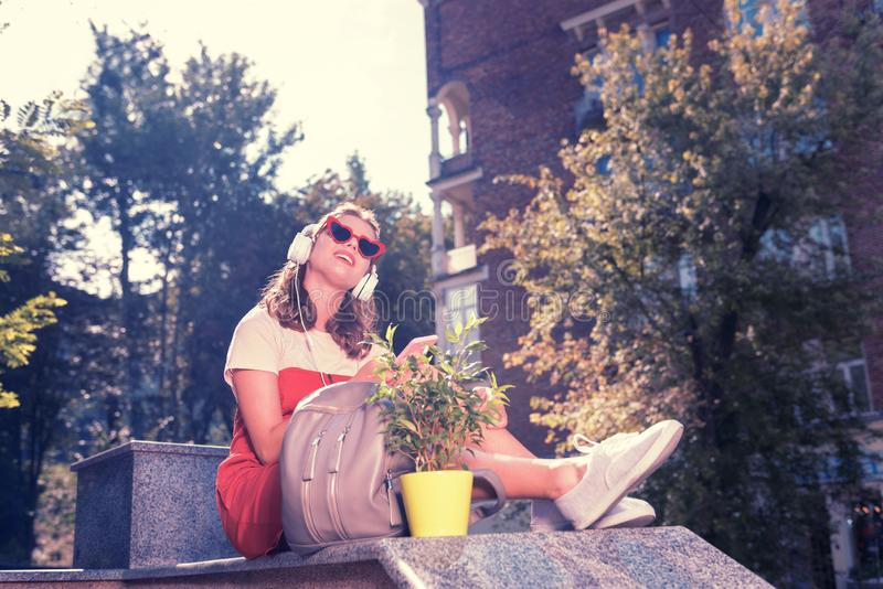 Appealing woman sitting in the park after buying home plant for new apartment. Appealing woman. Appealing woman sitting in the park after buying little cute home royalty free stock image