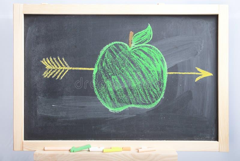 Appel en pijl op een schoolboard stock foto's