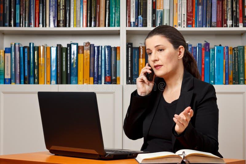 Appel téléphonique de bureau mûr de femme image stock