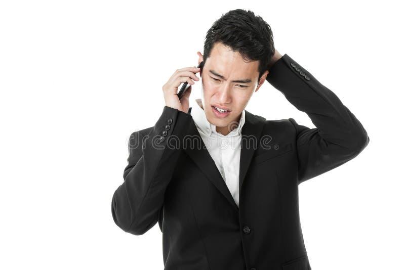 Appel téléphonique de réponse d'homme d'affaires perplexe photographie stock libre de droits
