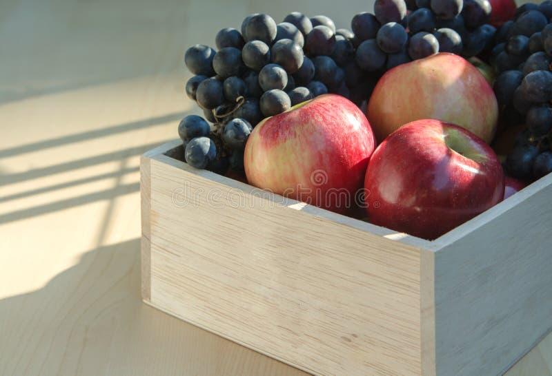 Appelen en druiven in een houten doos stock fotografie