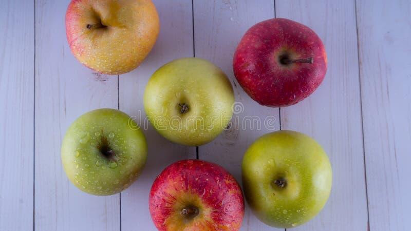 Appelen op een witte houten lijst Oogst van groene en rode appelen royalty-vrije stock afbeeldingen