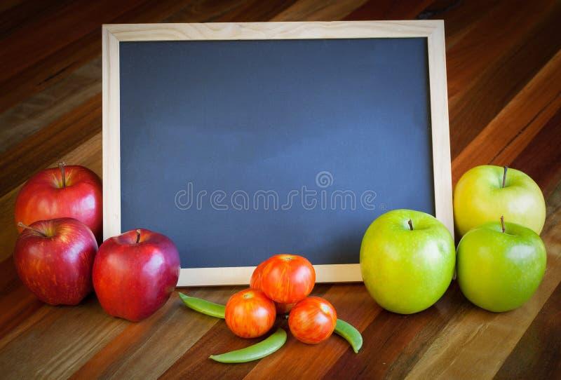 Appelen, tomaten, zonnebloem en bordsamenstelling royalty-vrije stock afbeeldingen