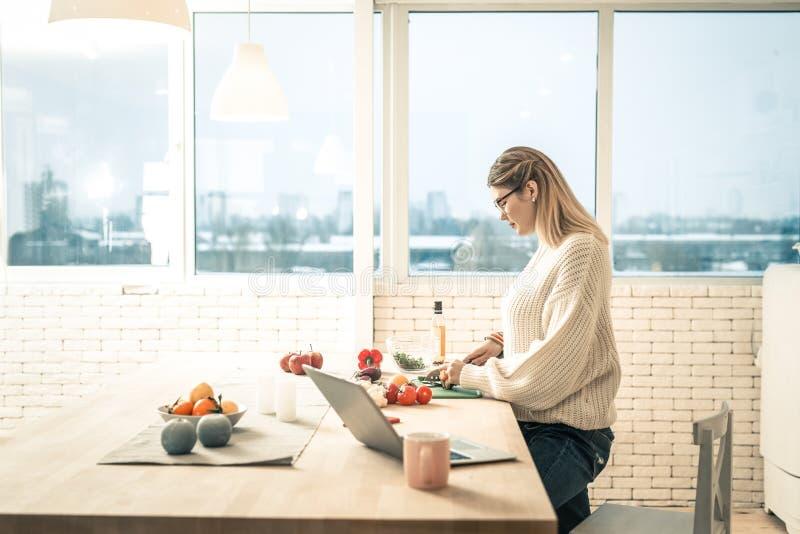 Appellera anseende för vuxen kvinna i kök och laga mat royaltyfria foton