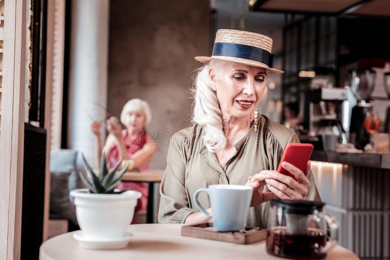 Appellera den långhåriga gamla kvinnan i sugrörhatt observera hennes smartphone royaltyfria bilder