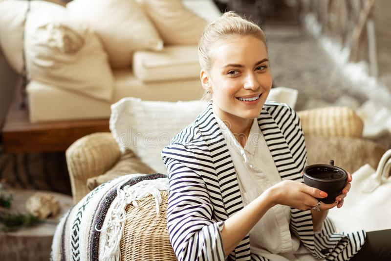 Appellera den positiva damen med bundet blont hår som vilar på en soffa fotografering för bildbyråer