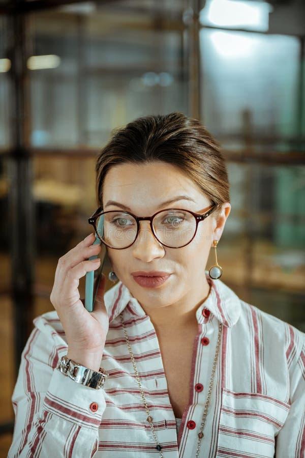 Appellieren der Frau, welche die blauen Ohrringe sprechen am Telefon trägt lizenzfreie stockfotos