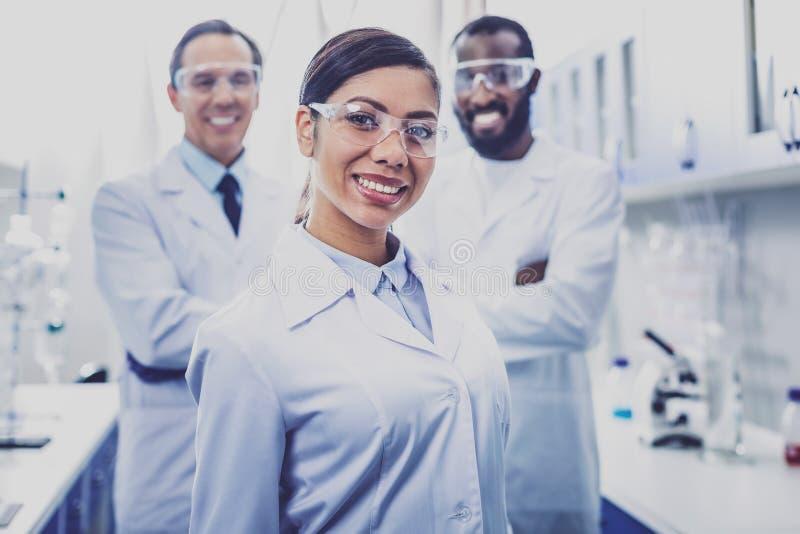 Appello del chimico sorridente che sta nel laboratorio fotografia stock