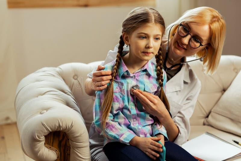Appello del medico che fa l'esame del polmone di una ragazza malata fotografie stock