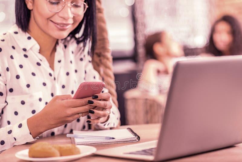 Appello della donna con arte scura del chiodo che tiene smartphone rosa mentre scrivendo messaggio a macchina fotografia stock libera da diritti