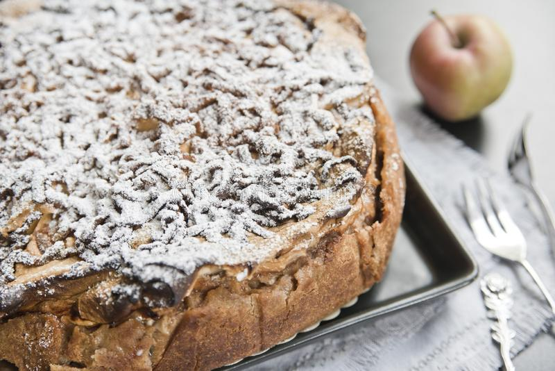 Appeltaart, gepoederde suiker, appel en uitstekende vorken stock fotografie