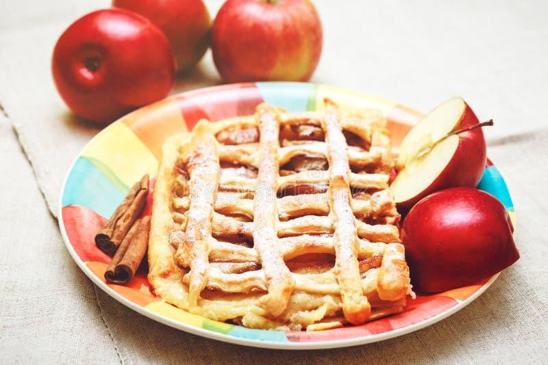 Appeltaart met Gebakjenet, Sugar Pouder, op de Ceramische Plaat met Gestemde Kaneel en Vers Apple, stock foto