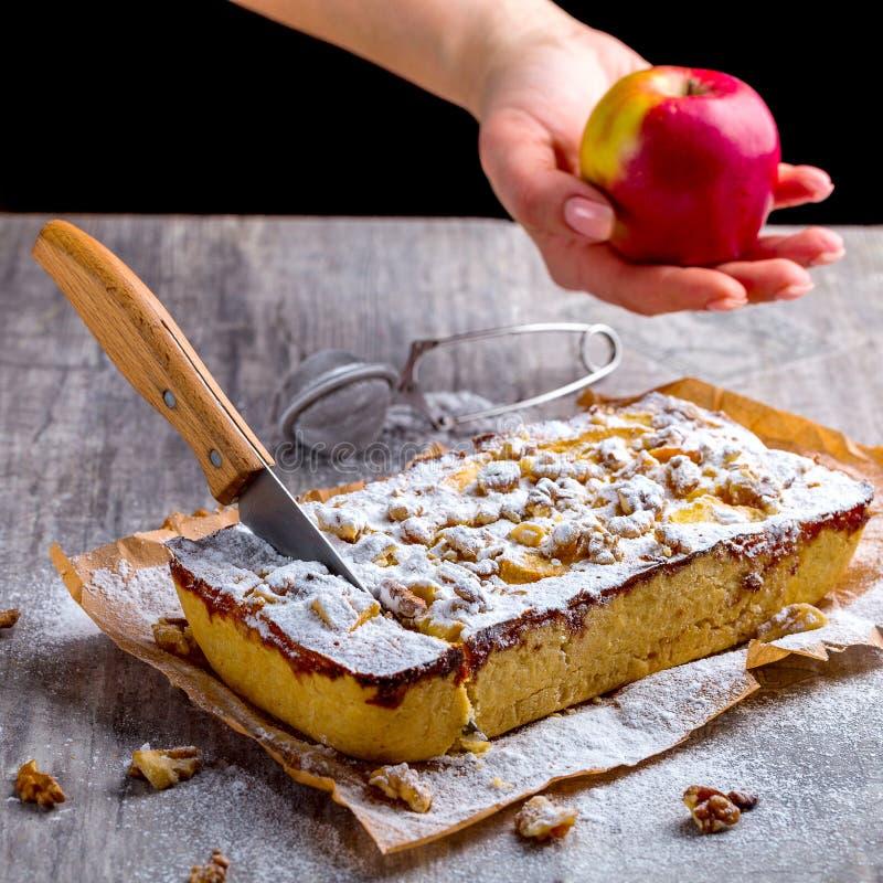 Appeltaart, met gepoederde suiker en besnoeiing met een mes wordt bestrooid dat Hand stock foto's